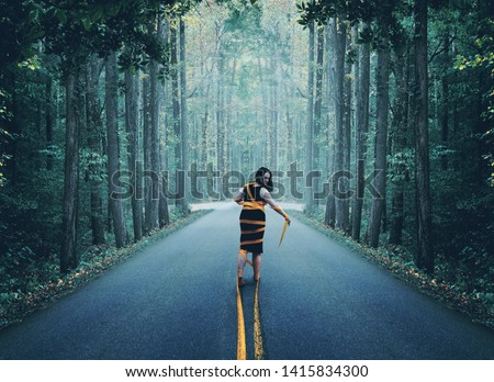 A woman wrapped up in the yellow road lines. Royalty-Free Stock Photo #1415834300
