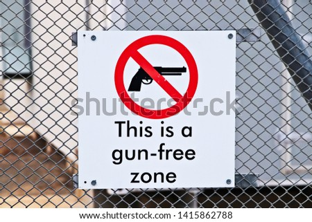 A Gun-free zone signpost on a fence. Gun control in America concept image.  #1415862788