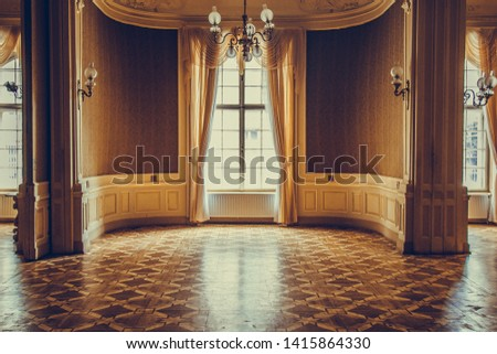 Lviv, Ukraine, 06.04.2019. wooden windows with vintage curtains and square moldings on a sunny day. beige satin curtains. interior of an empty room with luxury decorations and lamps on the walls. #1415864330