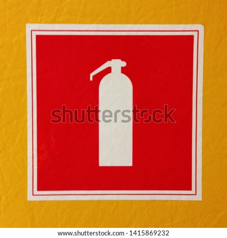 Macro photo sign fire extinguisher. Texture background banner red silhouette fire extinguisher hanging on the wall. Red fire extinguisher symbol on yellow wall background