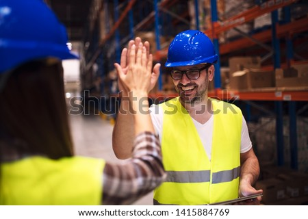 Friendship on job. Good relationship between two coworkers. Warehouse worker giving high five to his friend colleague. Workers hands touching and clapping for successfully done job in warehouse.