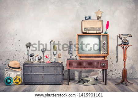 Retro TV, old studio microphones, outdated broadcast radio, journalist's reel tape recorder, aged telephone, film camera, golden award star, quill, typewriter. Journalism concept. Vintage style photo #1415901101