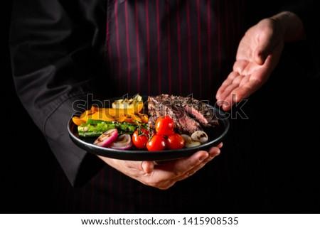 Grilled and sliced beef steak with grilled vegetables served on black plate on black background.