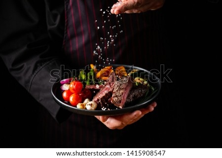 Grilled and sliced beef steak with grilled vegetables served on black plate on black background presentation in chef hands.