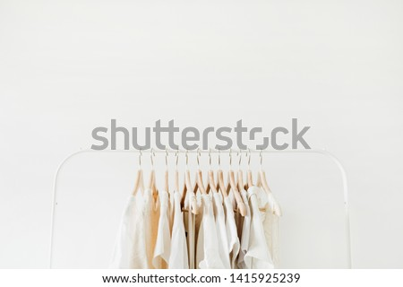 Minimal fashion clothes concept. Female blouses and t-shirts on hanger on white background. Fashion blog, website, social media hero header template. #1415925239
