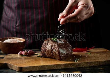 Chef hands cooking meat steak and adding salt and pepper on black copy space background for menu restaurant or recipe text. #1415930042