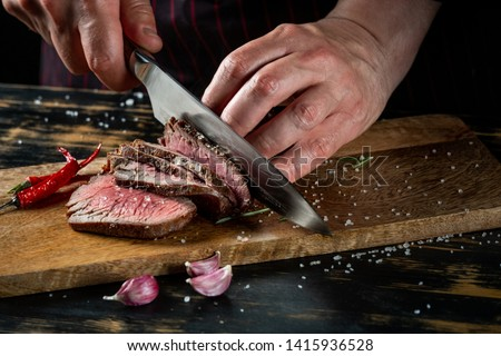 Cooking juicy beef steak by chef hands on dark black background with copy space for text menu or recipe. #1415936528