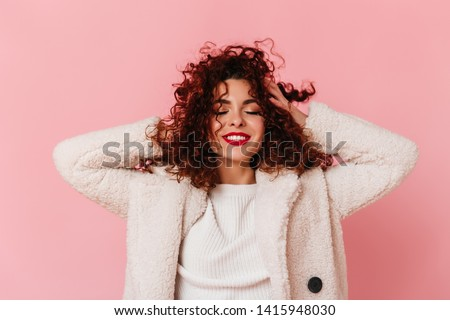 Portrait of charming lady with red lipstick and snow-white smile dressed in bright eco-coat and touching her curly hair on pink background Royalty-Free Stock Photo #1415948030