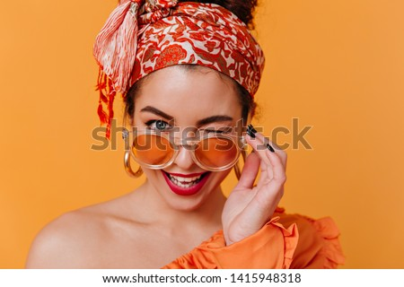 Lovely woman in African-style massive earrings and headband removes her orange glasses and winks coquettishly #1415948318