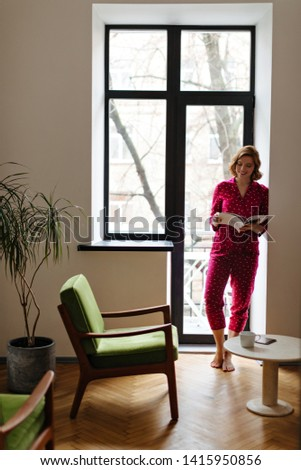 Full length view of smiling european woman reading magazing in morning. Indoor shot of lovely barefoot girl in pajama standing near window. #1415950856