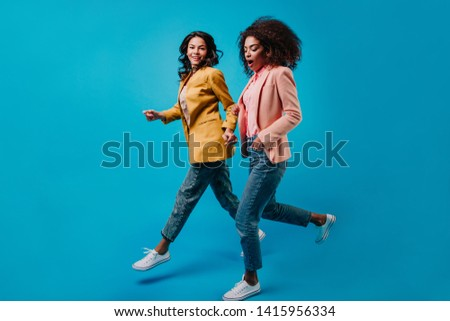 Funny african and latin girls dancing on studio background. Indoor full-length portrait of two jumping women. #1415956334