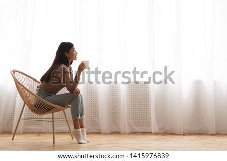Young Girl Sitting In Modern Chair, Enjoying Coffee In Front Of Window, Side View #1415976839
