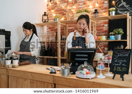 smiling waitress taking order on smartphone and using tablet in cafeteria. coffee shop staff talking online with customer while barista preparing beverage. two girl colleagues work together in cafe #1416011969