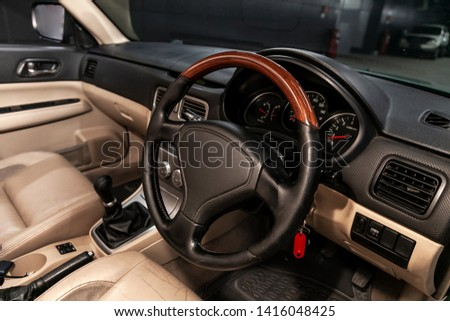 Close-up of the dashboard, speedometer, tachometer and steering wheel with wooden inserts with phone setting and volume buttons. Luxurious car interior details
