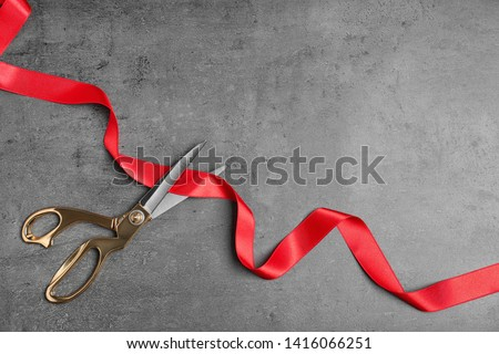 Stylish scissors and red ribbon on grey background, flat lay with space for text. Ceremonial tape cutting #1416066251