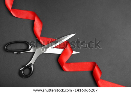 Stylish scissors and red ribbon on black background, flat lay with space for text. Ceremonial tape cutting #1416066287