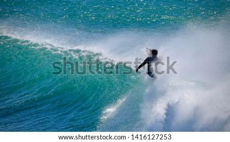 Malibu, CA USA - January 24 2015: A surfer makes a cut as a waves crests. #1416127253