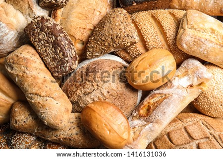 Different kinds of fresh bread as background, top view #1416131036