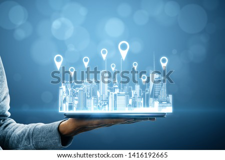 Close up of hand holding tablet with city hologram and location pins on blurry background with bokeh circles. Map and innovation concept #1416192665
