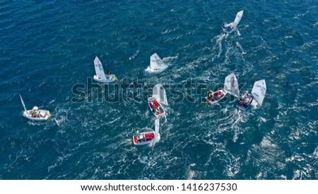 Porto Rafti, Attica / Greece - June 02 2019: Aerial drone bird's eye view photo of small sail boats operated by children cruising in bay of Porto Rafti #1416237530