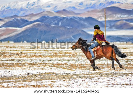 the mongolian kazakhs of western mongolia migrate each year with their herd of camels. horses, sheep, cows and goats in the snowy altai mountain, from camp to camp #1416240461