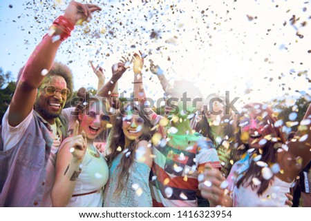Friends celebrating holi festival under shower of confetti #1416323954