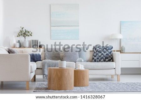 Two wooden coffee tables with plant in pot in front of grey corner sofa in fashionable living room interior Royalty-Free Stock Photo #1416328067