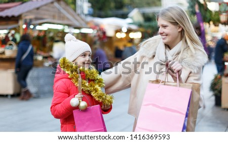 Portrait of smiling teen girl with mother holding shopping bags with purchases on street Christmas market #1416369593