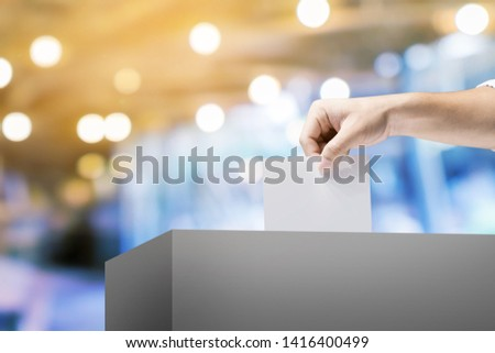 Hand holding ballot paper for election vote concept. #1416400499
