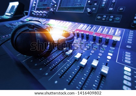 Professional audio studio sound mixer console board panel with recording , faders and adjusting knobs,TV equipment. Blue tone and close-up image with flare light effect. Royalty-Free Stock Photo #1416409802