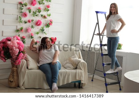 Two pretty girls in jeans and white T-shirts in a room with flowers. One of the girls with a fat build, and the other with a thin one. Positive girls posing in the studio on the couch in funny poses. #1416417389