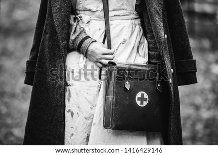 Re-enactor Wears Historical German Nurse Paramedic Of World War II Uniform With First Aid Kit. Photo In Black And White Colors. WWII WW2. Royalty-Free Stock Photo #1416429146