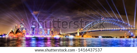 WIde panorama of Sydney city CBD landmarks and high-rise office buildings on waterfront of Harbour with the Sydney harbour bridge at Vivid Sydney light show illumination. Royalty-Free Stock Photo #1416437537