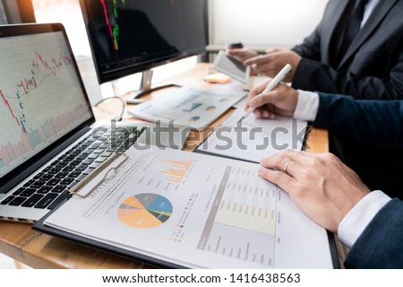Team of stockbrokers Discussing with display screens Analyzing data, graphs and reports of stock market trading for investment  #1416438563
