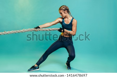 Tough young woman exercising with battling rope in studio. Healthy sports woman working out with battle rope over blue background. #1416478697