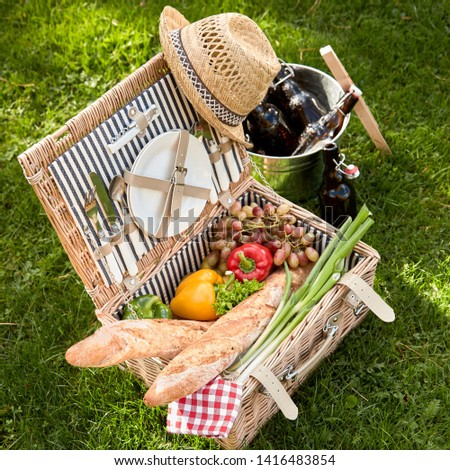 Health vegetarian and vegan picnic lunch with fresh salad ingredients and French baguettes packed into a wicker hamper alongside a silver wine cooler with bottles of beer on green grass #1416483854