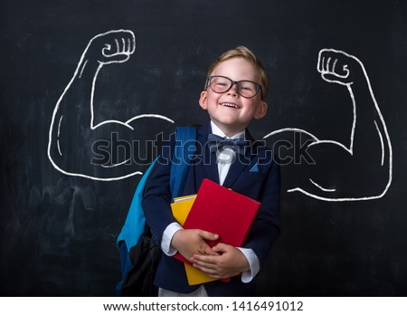 Cute child boy in school uniform and glasses. Go to school for the first time. Child with school bag and books. Kid in class room near chalkboard with muscles on it. Back to school #1416491012