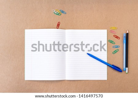 composition with notebook blank page colorful pencil, pen mock-up Back to school concept with stationery office supplies on a brown craft paper background with copy space top view #1416497570