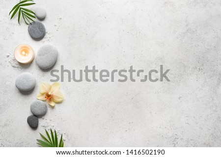 Spa concept on white stone background, palm leaves, flower, candle and zen like grey stones, top view, copy space. #1416502190