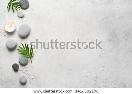 Spa concept on white stone background, palm leaves, candle and zen like grey stones, top view, copy space.