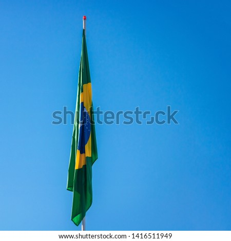 Brazilian flag on pole without wind in front of blue sky.  #1416511949