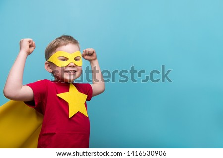 Little child superhero with yellow cloak and star. Happy smiling kid in glasses ready for education. Success, motivation concept. Back to school. Little businessman isolated on blue, Boy superhero.  Royalty-Free Stock Photo #1416530906