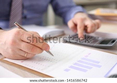 Accountant Calculate Finance Company Expenses. Man Accounting Financial Data Using Calculator, Graph, Stationery at Workplace. Secretary Analyzes Economy Revenue. Payment Growth Calculation #1416586742