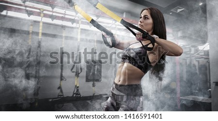 Sport. Women training with fitness trx straps in the gym. Beautiful lady exercising her muscles sling or suspension straps.  #1416591401