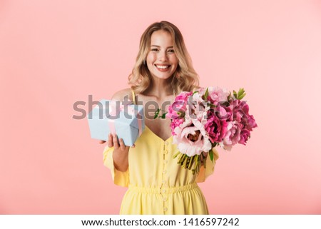 Image of a beautiful excited young blonde woman posing isolated over pink wall background holding flowers holding present gift box.