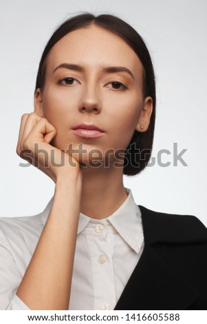 Portrait of a beautiful pacified woman in a white shirt and black jacket. Studio photo session. White background #1416605588