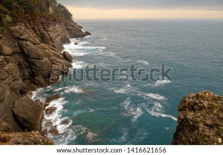 Sea view from a rocky cliff of the Regional Natural Park of Portofino in the Levante Riviera with waves crashing against the rocks and cloudy sunset sky on the horizon over sea, Genoa, Liguria, Italy #1416621656