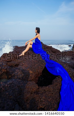 fashion pretty female model posing on a beach with rocks in a long butterfly chameleon dress waterfall of skirt plume train.sensual perfume with a beautiful and young brunette woman wave tropical sand #1416640550