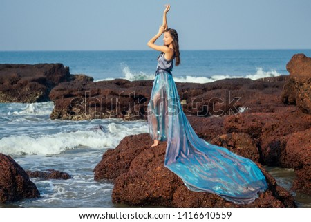 fashion pretty female model posing on a beach with rocks in a long butterfly chameleon dress waterfall of skirt plume train.sensual perfume with a beautiful and young brunette woman wave tropical sand #1416640559