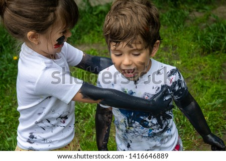 Children playing in mud, dirty cloth, messy face and hands in mud. Stains on clothes. Dirty cloth, washing laundry concept. #1416646889